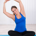 Female On Exercise Mat Doing Yoga At Home